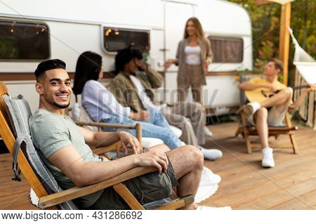 Group Of Multiracial Young Friends Having Outdoor Party Near Camper Van, Playing Guitar, Having Fun