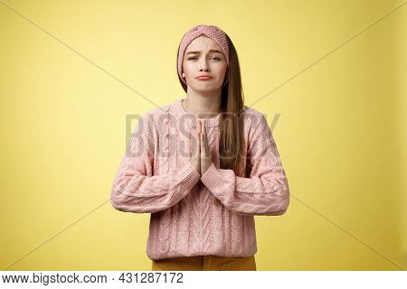 Deliberately Sad Girl In Sweater Pressing Palms Together In Pray Pouting Praying For Help, Asking Fa