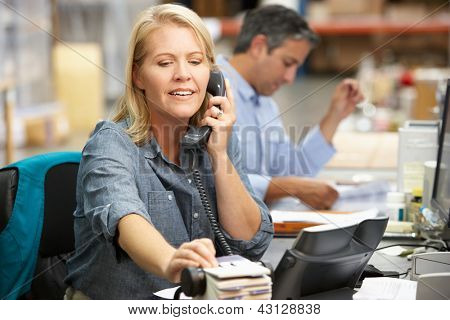 Businesswoman Working At Desk In Warehouse poster