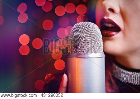 Female Singer With Disco Mic On Bokeh Light Background. Close-up Of Womens Lips Painted With Burgund