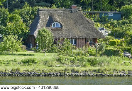Sunny Scenery Including A Reed Thatched House Around Travemuende In Germany