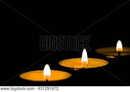 Burning Three Candles Selective Focus In Dark Isolated On Black Background With Copy Space. Concept