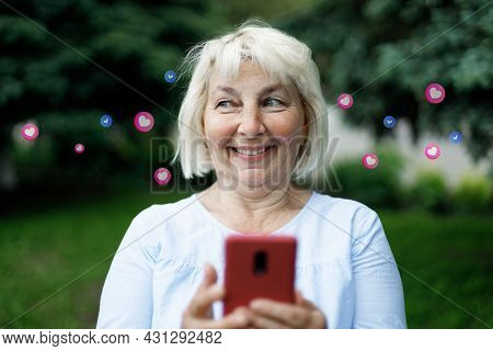 Shot Of Smiling Blonde Woman Using Her Mobile Phone, Reading Messages On Mobile Phone In The City Pa