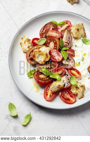 Salad With Tomatoes, Stracciatella, Ciabatta And Basil On A Light Background