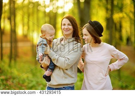 Family Of Three In Autumn Park. Cute Little Baby Boy In His Mothers Arms. Mom And Children Having Fu