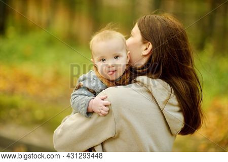 Cute Little Baby Boy In His Mothers Arms. Mom And Son Having Fun On Sunny Autumn Day In City Park. S