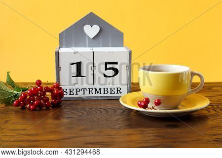 Calendar For September 15 : The Name Of The Month In English, Cubes With The Number 15, A Yellow Cup
