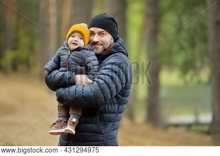 Cute Little Baby Boy In His Fathers Arms. Dad And Son Having Fun On Cold Autumn Day In City Park. So