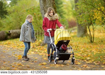Cute Big Sisters Walking In A Park With Baby Brother In Pushchair. Siblings Walk In City Park. Girls