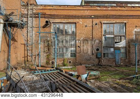 The Territory Of An Old Abandoned Factory Littered With Dismantled Metal Structures. Dangerous Place