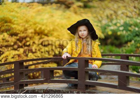 Cute Young Girl Wearing Black Witch Hat Having Fun Outdoors. Kid Trick Or Treating On Halloween. Fam