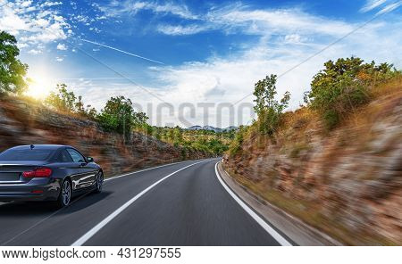 Black Car On A Scenic Road. Car On The Road Surrounded By A Magnificent Natural Landscape.