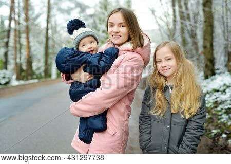 Two Big Sisters And Their Baby Brother Having Fun Outdoors. Two Young Girls Holding Their Baby Boy S