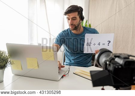 Online Education. Handsome Man Teacher With Headset Showing Blank Paper Sheet For Teaching Online At