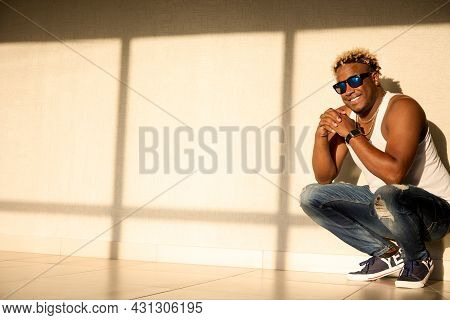 Young African American Man With A Snow-white Smile Wearing Sunglasses And A White T-shirt Is Squatti