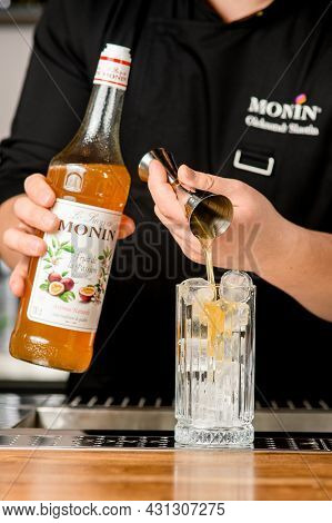 Ukraine, Kyiv - March 11, 2021: Bartender Pours Delicious Syrup From Jigger Into Crystal Glass With