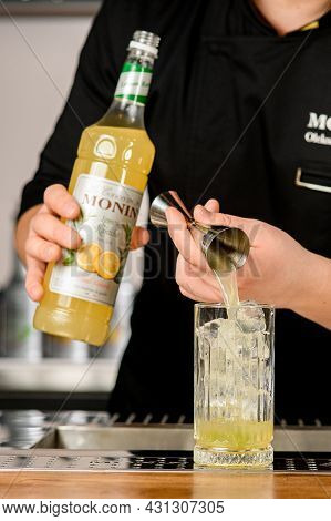 Ukraine, Kyiv - March 11, 2021: Bartender Pours Delicious Lemon Syrup From Jigger Into Crystal Glass