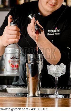Ukraine, Kyiv - March 11, 2021: Bartender Holds Jigger And Skillfully Pours Drink Into Shaker. Bottl