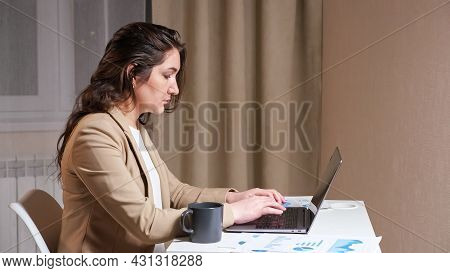 Concentrated Woman Freelancer With Long Loose Waving Hair Types On Grey Laptop Looking Into Display