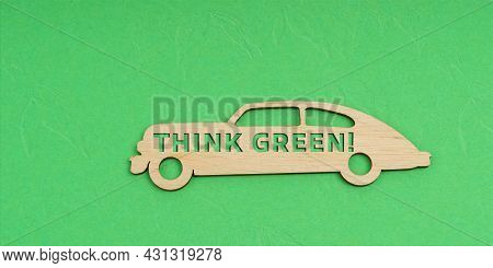 Ecology And Transportation Concept. On A Green Background, A Wooden Car With The Inscription - Think