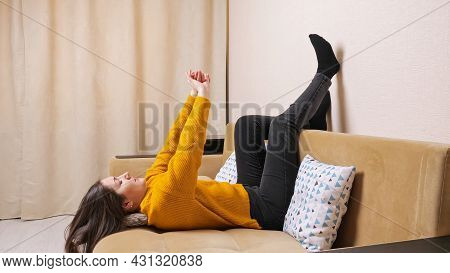 Bored Young Woman In Yellow Sweater Lies Lifting Legs Across Brown Sofa And Dances With Hands Among