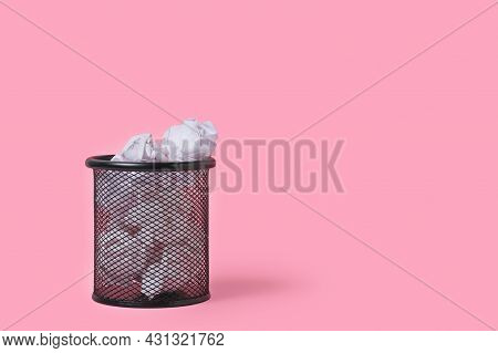 Crumpled Paper In Stationery Wastebasket On Pink Background