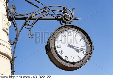 Antique Round Clock With Roman Numerals Hang On The Street Of The City