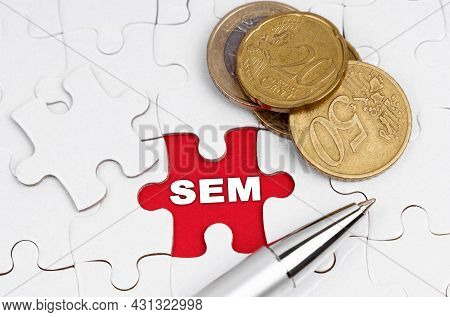 Business Concept. On White Puzzles There Are Coins And A Pen, In The Open Cell There Is An Inscripti