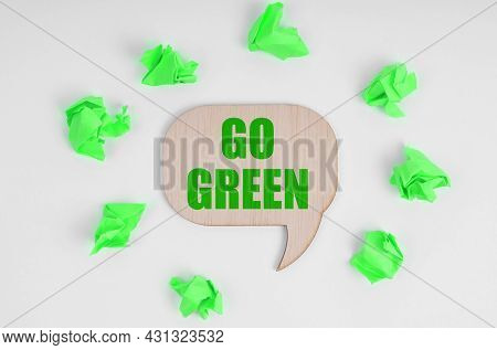 Ecology Concept. On A White Background, There Are Crumpled Green Pieces Of Paper And A Wooden Sign W