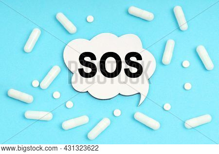 Medicine Concept. On A Blue Background Pills And A Plate. Inside The Sign It Says - Sos