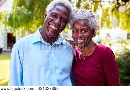 Portrait Of Relaxed Senior Couple Standing In Garden At Home After Retirement