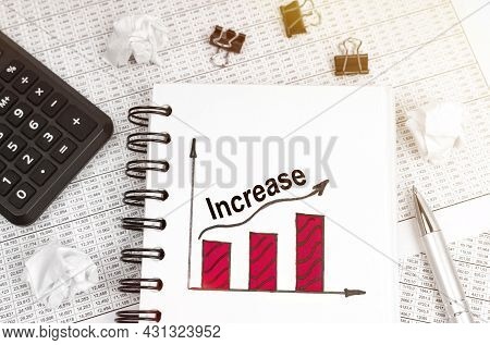 Business And Finance Concept. On The Table Is A Calculator, A Pen And A Notebook With A Graph And An