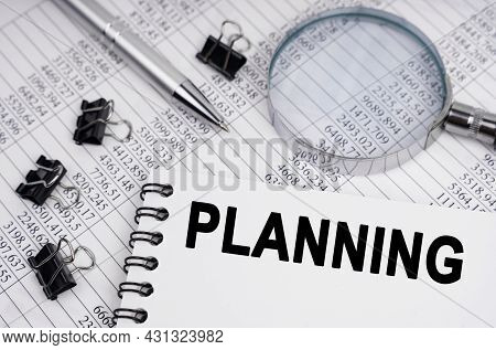 Business And Economics Concept. On The Table Is A Magnifying Glass, Reports, A Pen And A Notebook Wi