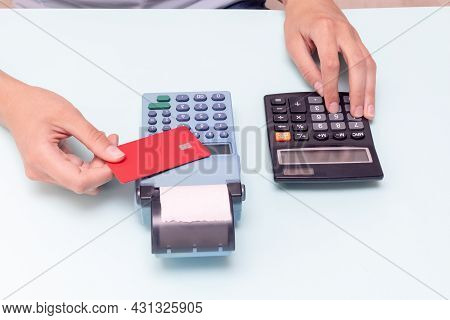 Payment For Purchases By Credit Card. Holding A Credit Card Over The Cash Register And Calculating T
