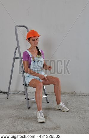 On A Construction Ladder The Foreman Sits In A Helmet