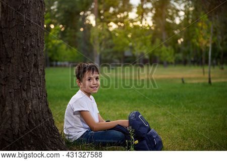 Beautiful Handsome Child School Boy Resting Sitting On Green Grass At The Park, Enjoying Recreation