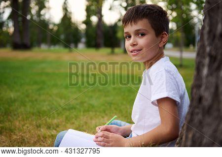 Side Portrait Of Handsome Elementary Aged Clever Boy Student, Intelligent Schoolboy Doing Homework,