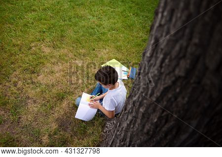 Top View Of A Clever Schoolboy Doing Homework, Writing On Copy Book, Solving Mathematics Tasks, Sitt