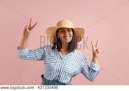 Smiling Positive Woman With Dark Hair Shows Peace Sign With Both Hands, Feels Excited To Go On Vacat