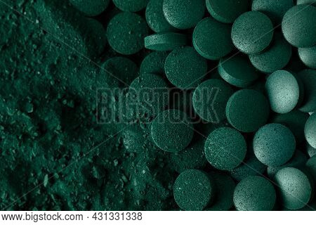 Green Spirulina Algae Tablets And Powder Nutritional Supplement Macro Close Up Top View.
