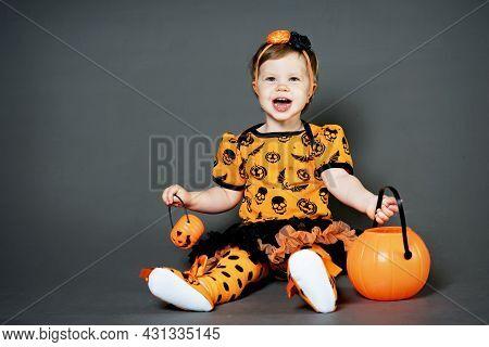 Little Girl In Halloween Costume With Pumpkin Jack. Happy A Child In The Studio, Grimacing And Horro