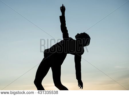 Being Flexible. Female Silhouette On Sunset. Woman Dance In Dark. Dark Figure Shape.