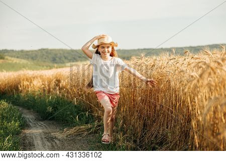 Happy Child With Hat On His Head Spends His Childhood In The Country, Runs Happily Next To The Wheat