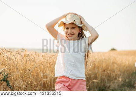 Kid Girl With Hat, Happy Smiles Beautifully While In Golden Wheat Field. Childhood In The Countrysid