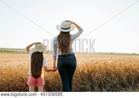 Rear View Of Family Farmer Woman And Child With Hat On Golden Wheat Field At Sunset