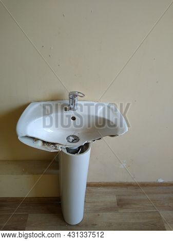 White Porcelain Washbasin In A Broken State In An Office Room. High Quality Photo