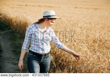 Young Woman Farmer In Wheat Field Examining Crop At Sunset. Young Female Farmer With Hat And Shirt I