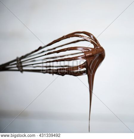 Chocolate sauce on a whisk