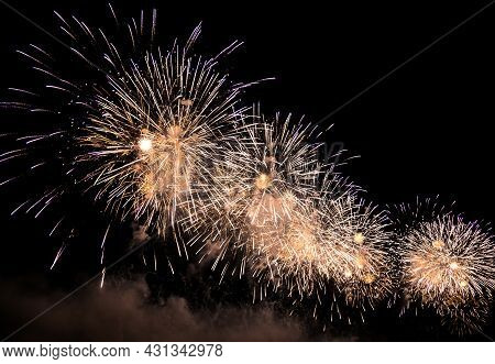 Beautiful Fireworks In The Night Sky During The Holiday, Golden Sparks And Firecrackers. New Year's