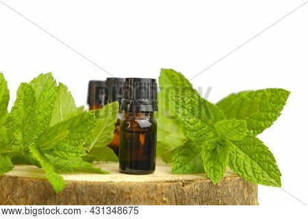 Peppermint Essential Oil Isolated On White Background.glass Bottles And Sprigs Of Mint On A Wooden S